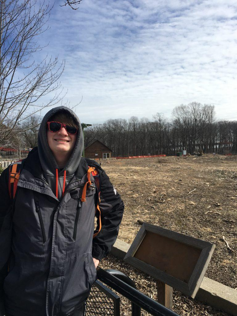 My brother, Ryan, smiles sarcastically next to the bulldozed woods and fields. - Photo by Maddie Steger