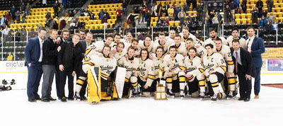 The hockey team celebrates with the MacInnes cup after winning the Winter Carnival series against Bemidji State.