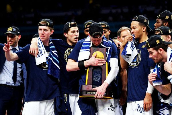 Villanova guard Donte DiVencenzo holds the trophy while the team celebrates the win.