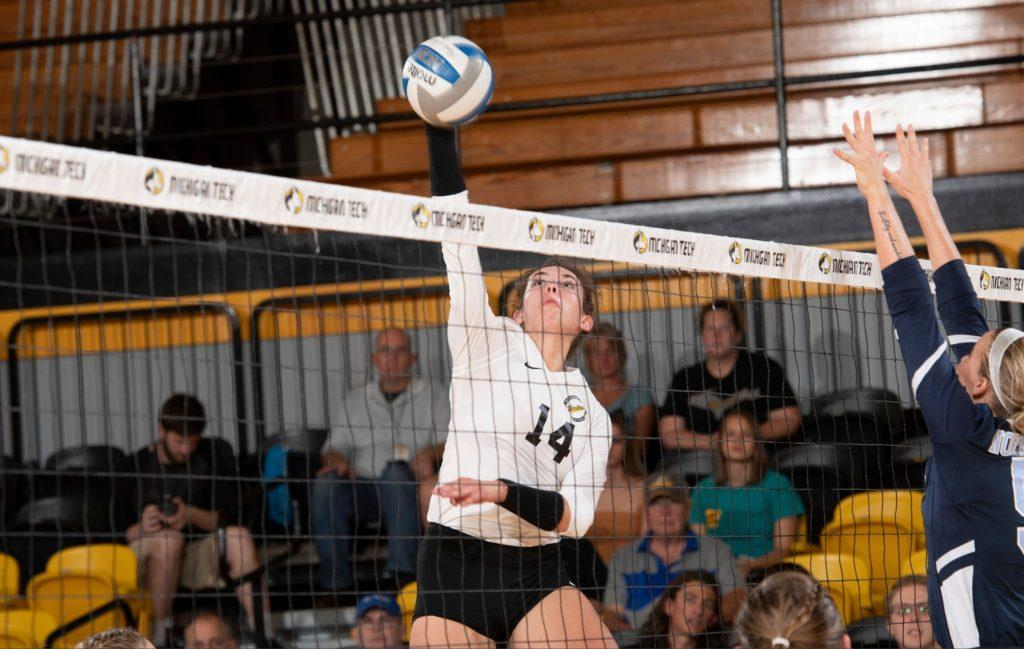 Olivia Ghormley reaches for the volleyball above the net during the match against Northwood.