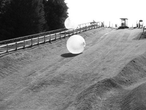 Some participants of Zorbing rolling down a hill in the giant plastic ball.