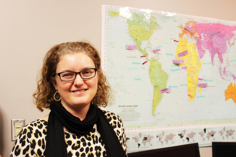 Kari Henquinet poses near a map overlooking  her office in the Pavlis Honors College.