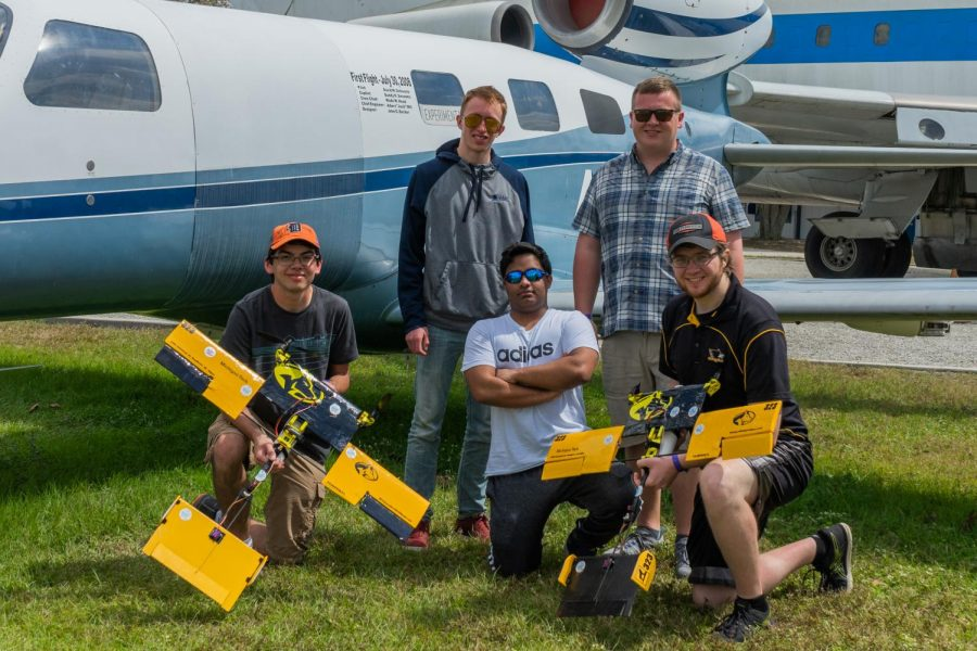(Above) SAE Aero Design members are seen here, from left to right: Noah Baliat, Ry Swaty, Rithik Sawant, Andrew Erickson, and Alex Mathias (Below) One of the aircraft designs created by club members.